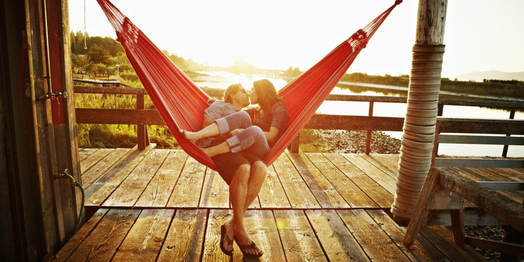 Husband and wife couple kissing in hammock