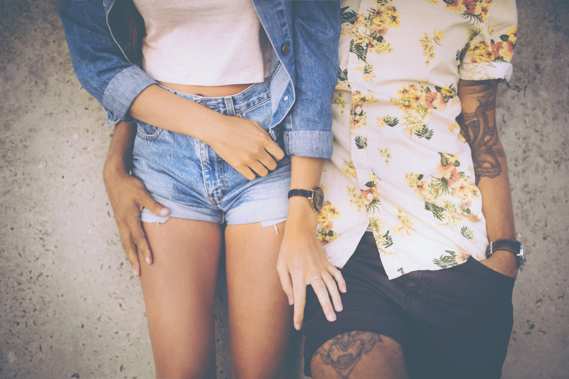 Cropped midsection of a hipster couple standing close together and leaning against a wall in retro style clothing