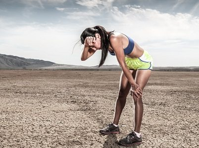 A women athlete bent over in an arid desert envirnoment.