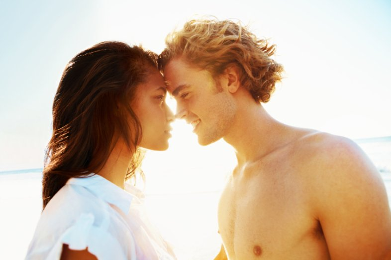 A young couple gazing into each other's eyes on the beach